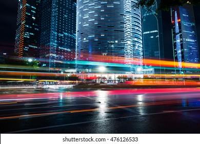 die Lichtspuren auf dem modernen Gebäudehintergrund