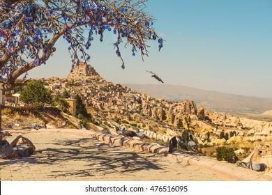 Tauben, die im Tauben-Tal in Kappadokien, Türkei fliegen. Baum voller hängender Nazar-Amulette, spezielle augenförmige Gegenstände, die vor dem bösen Blick schützen sollen.