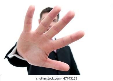 """Ein Geschäftsmann Mitte dreißig in einem schwarzen Anzug bedeckt die Kamera mit seiner Hand. """"Es gibt hier nichts zu sehen"""". Differenzieller Fokus auf die Hand."""