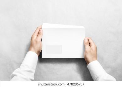 白色空白信封嘲笑舉行手中。與透明窗口設計樣機的空字母。消息模板演示。人打開清晰的郵件。