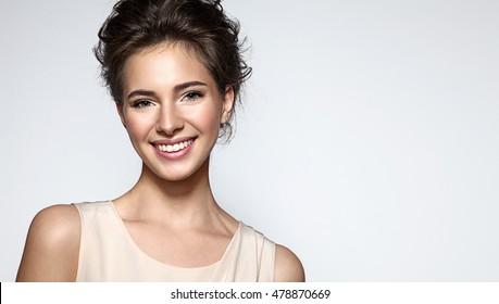 きれいな肌、ナチュラルメイク、灰色の背景に白い歯を持つ笑顔美人