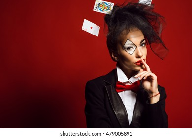 Retrato de una joven bella crupier con un bromista de maquillaje artístico y tarjetas voladoras sobre el fondo rojo. Concepto de juego y casino. Foto de estudio Espacio de copia