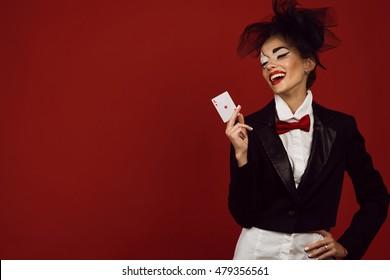 Porträt einer jungen schönen Dame Croupier mit einem künstlerischen Make-up-Joker auf dem roten Hintergrund, der eine Ass-Karte hält und lacht. Glücksspiel- und Casino-Konzept. Gewinner. Studioaufnahme. Kopierraum