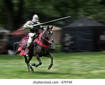 Jinete blindado con lanza a caballo. Movimiento de fondo borroso.