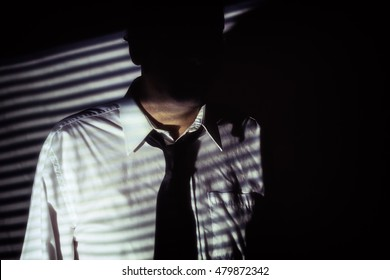 Faceless Shadow Man Interrogator. Mysterious, anonymous man with face hidden in shadows of blinds, wearing white shirt and black tie. Shot in film noir style.