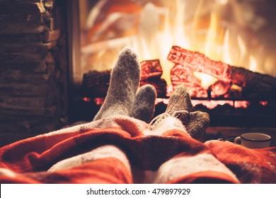 Kalter Herbst- oder Winterabend. Menschen, die mit Decke und Tee am Feuer ruhen. Nahaufnahmefoto von Füßen in Wollsocken. Gemütliche Szene.