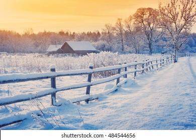 Ländliches Haus mit einem Zaun im Winter. Dorf nach Schneefall