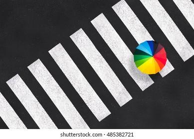 Top view of a rainbow umbrella on a pedestrian crosswalk