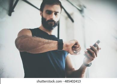 トレーニングセッション後の写真ひげを生やしたスポーティーな男は、フィットネスの結果をチェックしますスマートフォン。スポーツトラッカーリストバンドアームを身に着けている大人の男。ジム内でハードトレーニング。水平バーの背景。ぼやけた
