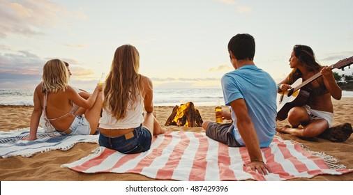 夕暮れ時のビーチで焚き火の周りでリラックスした友人のグループ