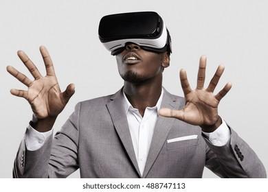 Technologie-, Spiele-, Unterhaltungs- und Personenkonzept. Afrikanischer Mann, der formellen Anzug und Virtual-Reality-Headset oder 3D-Brille trägt, Videospiel spielt, mit seinen Händen gestikuliert und etwas fängt