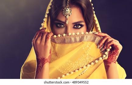 美しいインドの女の子。タトゥー一時的な刺青とクンダンジュエリーの若いヒンドゥー教の女性モデル。伝統的なインドの衣装黄色のサリー。インド人またはイスラム教徒の女性が彼女の顔を覆っています。