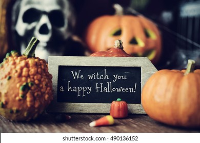 a chalkboard with the text We witch you a happy Halloween, surrounded by some different pumpkins, placed on a rustic wooden surface, and some scary ornaments, such as a skull or a carved pumpkin