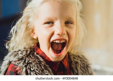 日当たりの良い公園で真っ青な目を持つヒスパニック系の女の子の肖像画。緑の葉と屋外で笑顔の少女。都会の設定で小さな女の子がカメラに微笑んでいます。