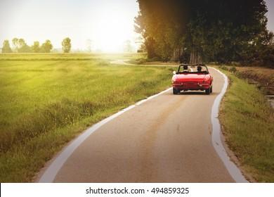 Klassisches rotes Cabrioauto, das im Land bei Sonnenuntergang reist