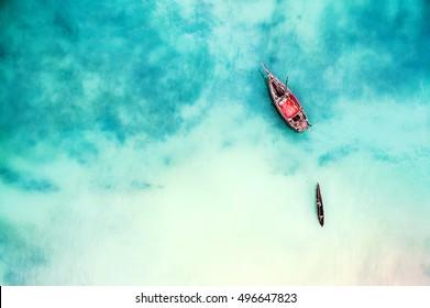 Barco y barco en el hermoso océano turquesa cerca de una isla, vista superior, foto aérea