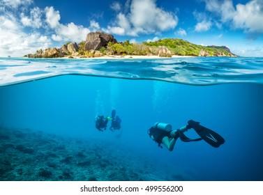 Taucher unter der Oberfläche auf den Seychellen erkunden Corlas