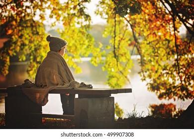 Lindo niño, niño, sentado en el borde de un lago en una soleada tarde de otoño, viendo cisnes nadando en el lago, hermosos colores otoñales