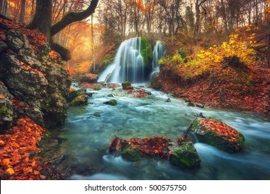 Autumn forest with waterfall at mountain river at sunset. Colorful landscape with trees, stones, waterfall and vibrant red and orange foliage. Nature background. Fall woods. Beautiful blurred water