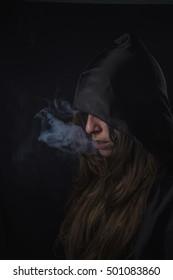 Attentäterin mit dunkler Kapuze, die Rauch aus ihrem Mund lässt, Gothic- und Halloween-Konzept