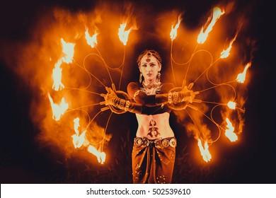 彼の手に火のファンで情熱的なダンスを踊る優雅な女の子。部族スタイルのダンサー。火ショー。