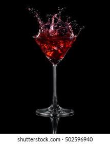 Eiswürfel fiel in ein Glas Traubensaft. Schwarzer Hintergrund
