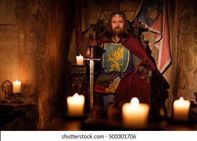 Alter mittelalterlicher König auf dem Thron im alten Schlossinneren.