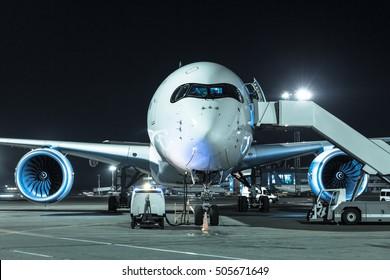 Avión de pasajeros estacionado en el aeropuerto de noche. Manejo de aviones y servicio de verificación previa. Vista frontal de la aeronave. Tono azul frío.