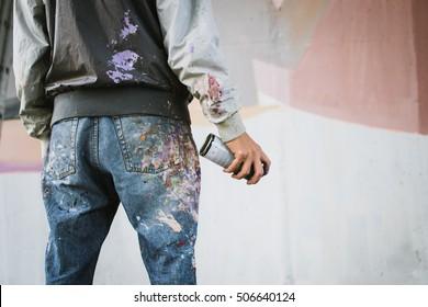 壁の近くにエアゾールスプレーボトルを持つグラフィティアーティスト