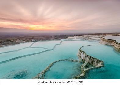 Travertinos de carbonato las piscinas naturales durante la puesta de sol, Pamukkale, Turquía