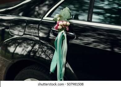 バラと緑のリボンの小さな花束がドアのハンドルに掛かっています