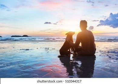 Freundschaftskonzept, Mann und Hund sitzen zusammen am Strand bei Sonnenuntergang