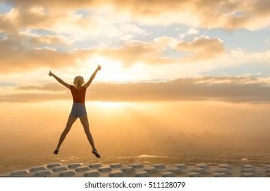 Concepto de éxito. Celebrando a la mujer encima de un rascacielos con vistas a la ciudad al amanecer.