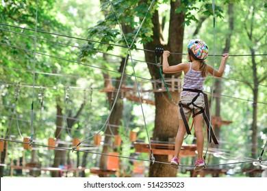 Abenteuer Klettern Hochseilpark - Mädchen auf Kurs in Berghelm und Sicherheitsausrüstung