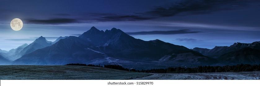 満月の光の中で夜の森と田園フィールドの背後にある霞のタトラ山脈のパノラマ