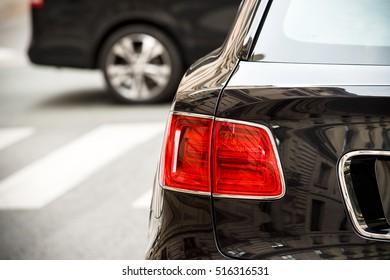 Detail eines roten Rücklichts eines Luxus-SUV, der in der modernen Stadt geparkt wird