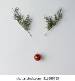 クリスマスの装飾と松の枝で作られたトナカイの顔。最小限のクリスマスコンセプト。フラット横たわっていた。