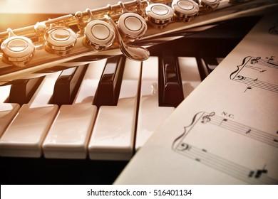 黄金の輝きと楽譜のあるピアノとフルート。水平方向の構成。正面図