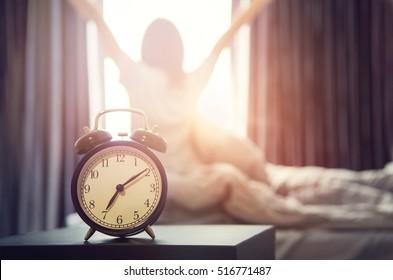 Nahaufnahmewecker, der einen guten Tag mit der glücklichen Frau des Hintergrunds im Bett nach dem Aufwachen, Sonnenlicht am Morgen streckt.
