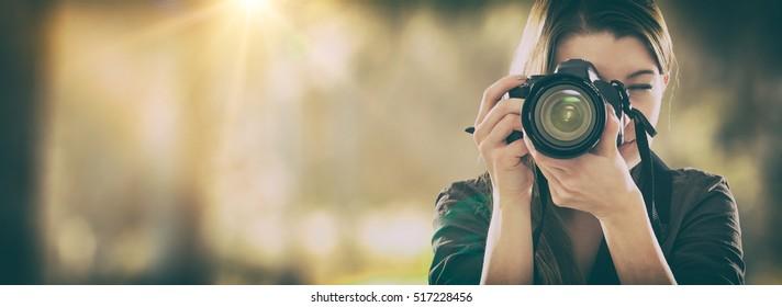 Retrato de un fotógrafo que cubre su rostro con la cámara.