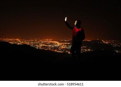 Junger Mann, der selfie oben auf dem Hügel nimmt, der die Nachtstadtansicht beobachtet.