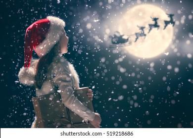 メリークリスマスとハッピーホリデー!クリスマスプレゼントのかわいい小さな子の女の子。月の空を背景にそりで飛んでいるサンタクロース。子供は休日を楽しんでください。暗い背景にギフトと肖像画の子供。