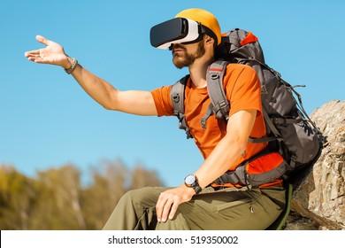 Erfolgreicher junger Mann, der Virtual-Reality-Brillen verwendet, um in den Bergen zu touren, im Sommer im Urlaub
