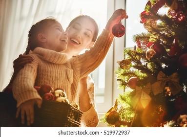 メリークリスマスとハッピーホリデー!ママと娘は室内でクリスマスツリーを飾ります。クリスマスの前の朝。家族を愛する肖像画をクローズアップ。