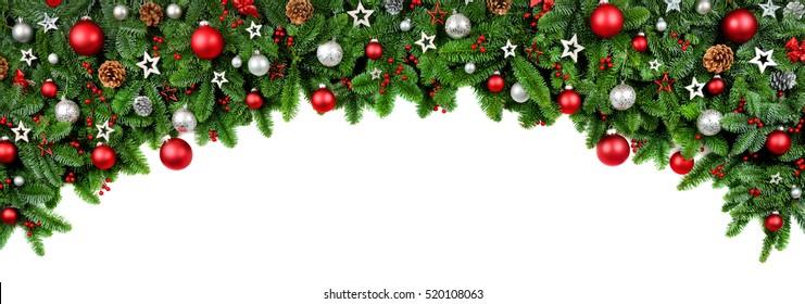 Breiter bogenförmiger Weihnachtsrand isoliert auf Weiß, bestehend aus frischen Tannenzweigen und Ornamenten in Rot und Silber