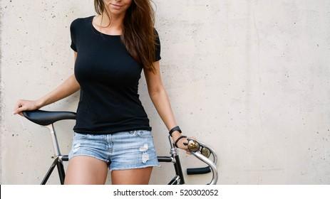 Ein abgeschnittenes Foto eines Mädchens mit langen braunen Haaren, das ein leeres schwarzes T-Shirt trägt, das auf einem Betonwandhintergrund auf einer Straße steht. Leerer Platz für Text oder Design.