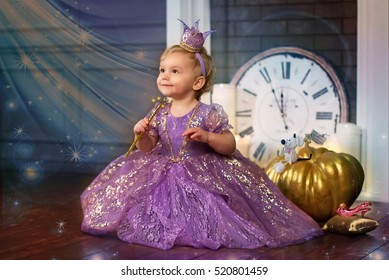 Little princess sitting near magic pumpkin and holding a magic wand in the hands of. Fairy tale. Very soft focus.