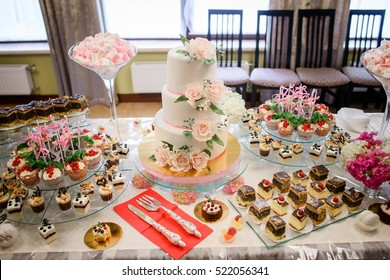 gentle white wedding cake and different sweets on table