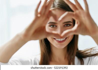Gesunde Augen und Vision. Porträt der schönen glücklichen Frau, die herzförmige Hände nahe Augen hält. Nahaufnahme des lächelnden Mädchens mit der gesunden Haut, die Liebeszeichen zeigt. Augenpflege. Hochauflösendes Bild