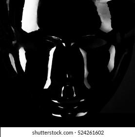 Glänzende schwarze Maskenschattenbild auf pechschwarzem Hintergrund.